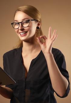 Garota profissional feliz usando óculos e segurando o tablet isolado no fundo marrom