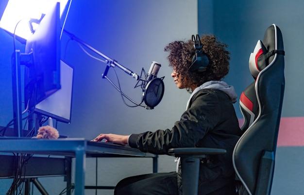 Garota profissional jogador joga videogame no computador dela. ela está participando do torneio de jogos cibernéticos on-line, joga em casa ou no cibercafé. ela usa fone de ouvido para jogos