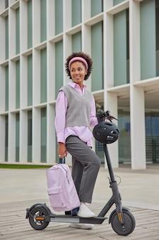 Garota pronta para descobrir a cidade urbana com scooter elétrica usa transporte urbano segurando mochila vestida com roupas casuais sorri agradavelmente desvia o olhar