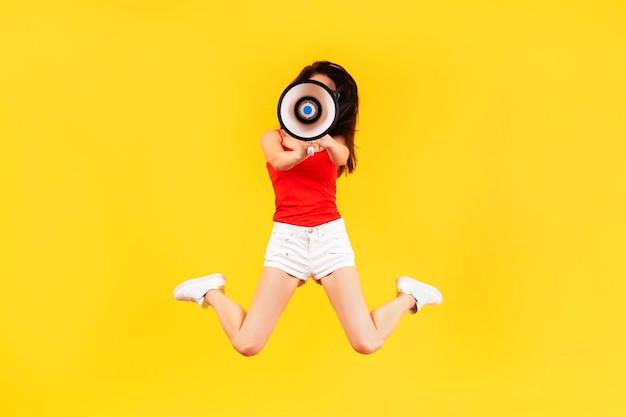 Garota pulando com um megafone em uma parede amarela