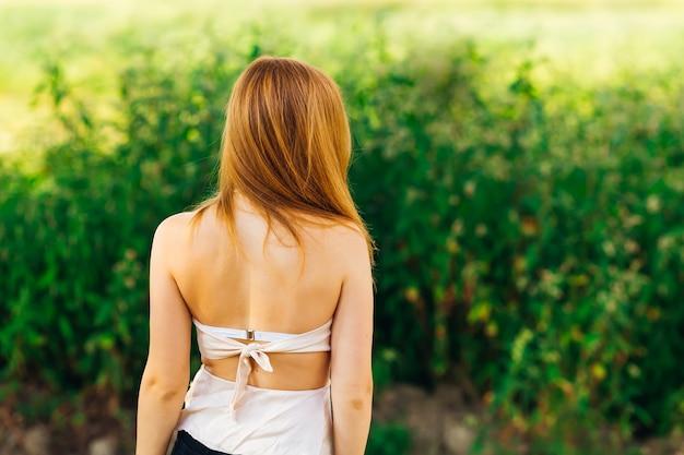Garota que está de costas para a câmera em um fundo de grama alta