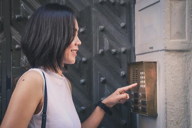 Garota que está pressionando um botão do interfone da casa ao ar livre em frente a uma enorme porta antiga.