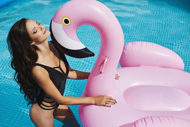 Garota quente e elegante modelo morena com corpo sexy perfeito em biquíni preto elegante e óculos de sol glamourosos posando com um flamingo rosa inflável na piscina