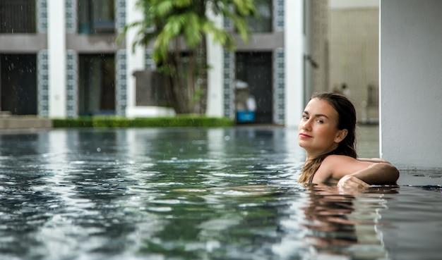 Garota relaxa na piscina