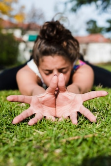Garota relaxada praticando ioga ao ar livre