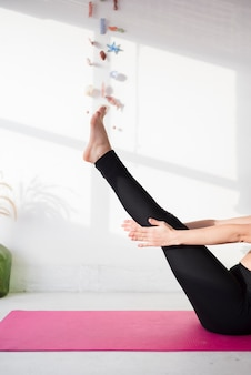 Garota relaxada praticando ioga em casa