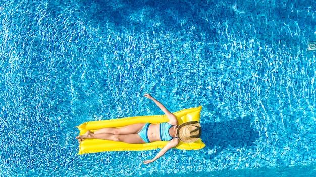 Garota relaxante na piscina, criança nada no colchão inflável e se diverte na água em férias em família, estância de férias tropical, vista aérea zangão de cima