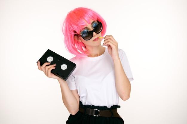 Garota retrô de óculos e peruca rosa segurando cassete preta sobre fundo branco.