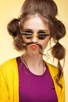 Garota retro engraçada com bigode feito de seu cabelo usando óculos escuros