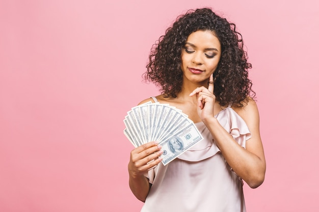 Garota rica! vencedor do dinheiro! pensando em uma linda mulher afro-americana em vestido segurando dinheiro isolado contra um fundo rosa.