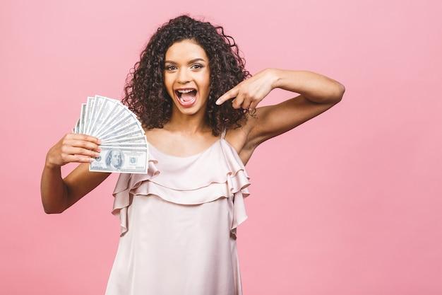 Garota rica! vencedor do dinheiro! surpresa linda mulher afro-americana no vestido segurando dinheiro e olhando para a câmera isolada contra o fundo rosa.