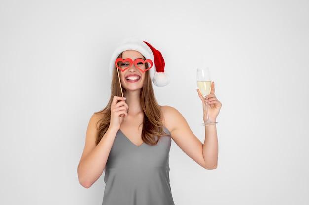 Garota rindo com chapéu de natal usando óculos escuros de mentira segurando taça de champanhe na festa de ano novo