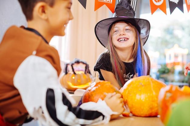 Garota rindo. linda garota engraçada usando fantasia de feiticeiro de halloween, rindo alto enquanto joga