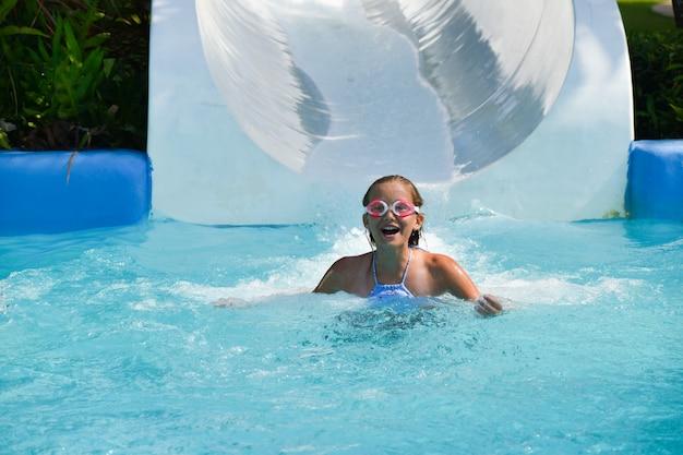 Garota rola um toboágua em um parque aquático
