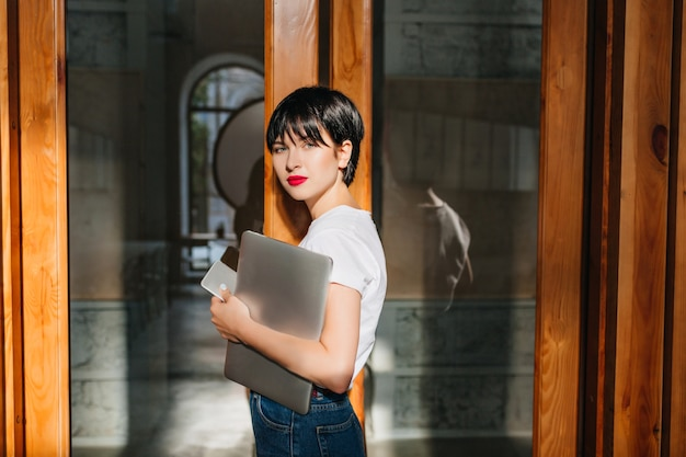 Garota romântica com penteado curto em pé perto da porta segurando um laptop e smartphone
