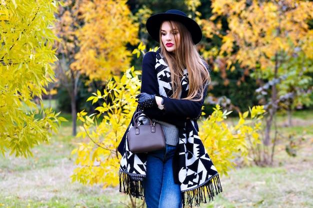 Garota romântica de óculos, segurando o chapéu e posando com beijar a expressão do rosto em pé no meio do parque. retrato ao ar livre de jovem bonito com lenço na moda se divertindo durante um passeio na floresta.