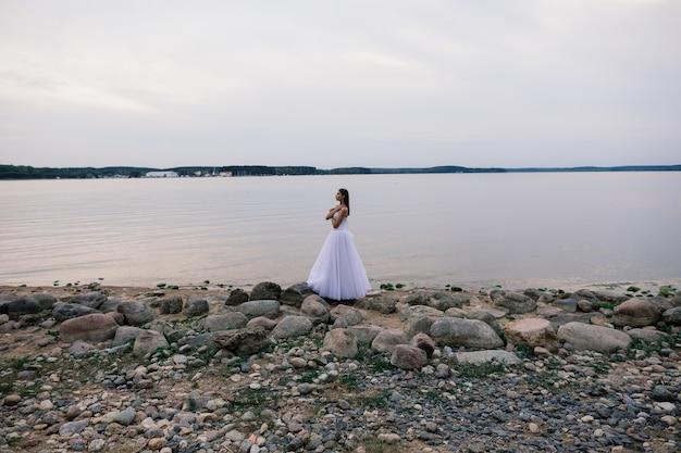 Garota romântica em um vestido branco macio na margem de um lago