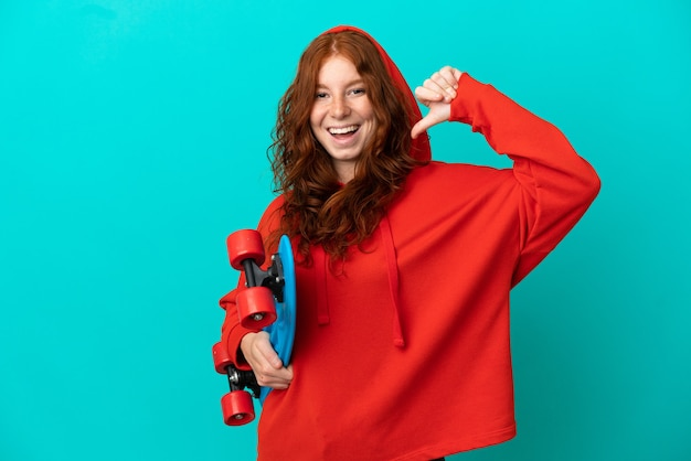 Garota ruiva adolescente isolada em um fundo azul com um skate e uma expressão feliz