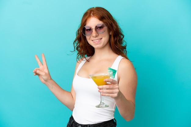 Garota ruiva adolescente isolada em um fundo azul em traje de banho e segurando um coquetel