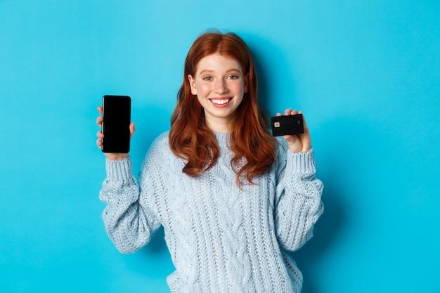 Garota ruiva animada mostrando a tela do celular e o cartão de crédito, demonstrando a loja online ou o aplicativo, de pé sobre um fundo azul.