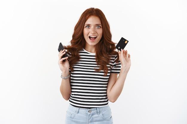 Garota ruiva atraente animada levantando smartphone e cartão de crédito, sorrindo fascinada e parecendo otimista, faça compras online em casa, insira o número do banco, compre roupas para o baile