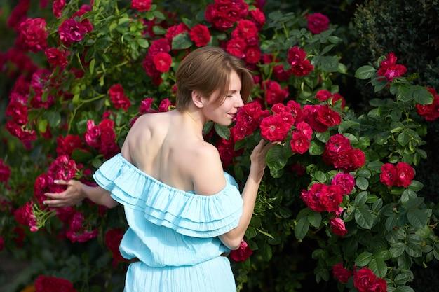 Garota ruiva atraente com penteado na moda usando elegante vestido azul claro cheirando rosas florescendo no jardim
