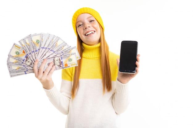 Garota ruiva atraente europeia detém dinheiro e um telefone com maquete de mãos em um branco