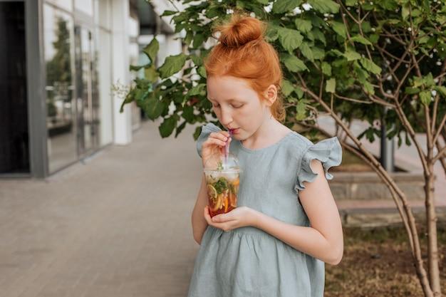 Garota ruiva bebe limonada em um copo de plástico.