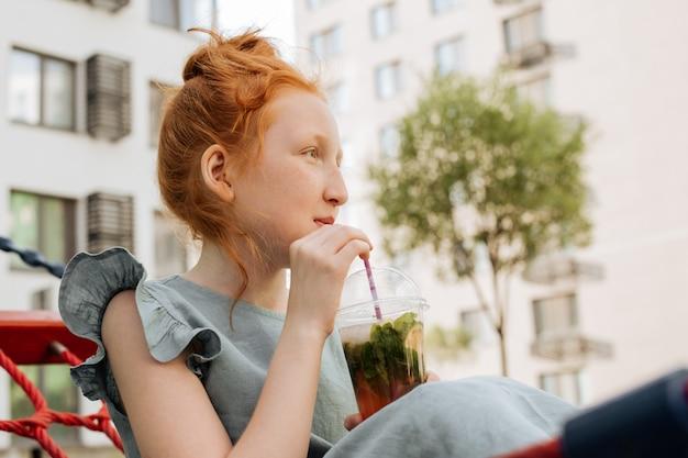 Garota ruiva bebendo limonada em um copo de plástico.