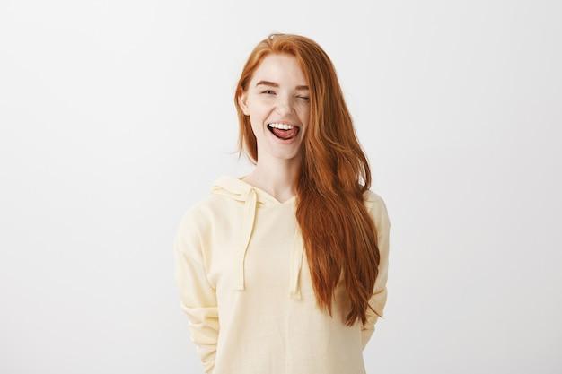 Garota ruiva bonita atrevida sorrindo feliz, piscando e mostrando a língua