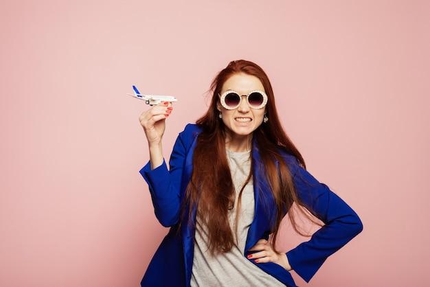 Garota ruiva bonita com raiva, engraçada e com babados em óculos de sol segura um modelo de avião em uma parede rosa. o conceito de viagens e vôos, problemas com viagens aéreas, perda de bagagem