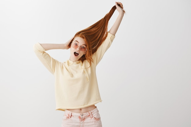 Garota ruiva bonita engraçada puxando o cabelo para cima e gritando