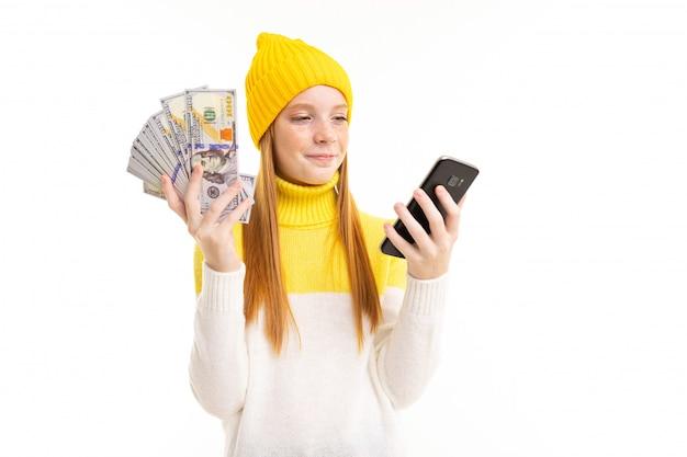 Garota ruiva bonita europeia, segurando o dinheiro com um telefone nas mãos em branco