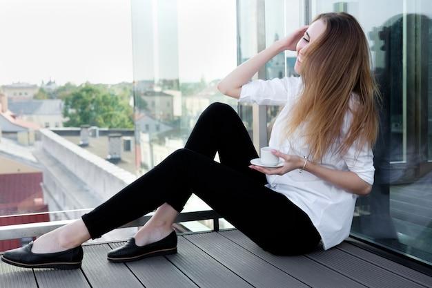 Garota ruiva branca na camisa branca, bebendo café