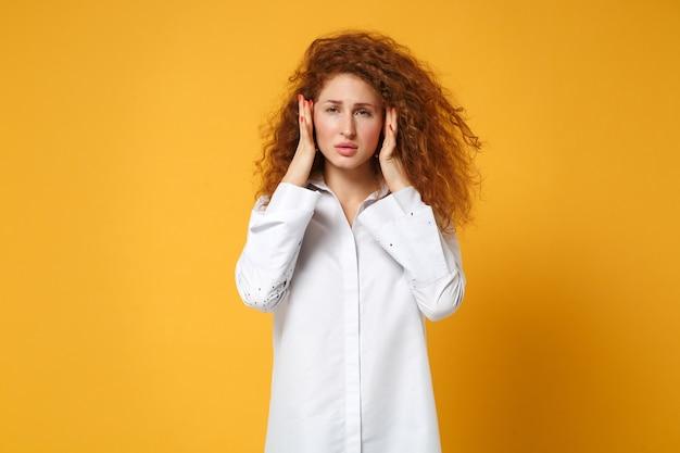 Garota ruiva cansada em uma camisa branca casual posando isolada em uma parede laranja amarela