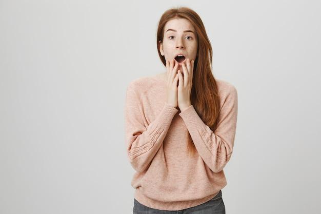 Garota ruiva chocada, ofegando, parecendo preocupada