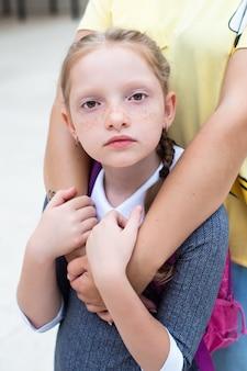 Garota ruiva, colegial parece triste. sardas e tranças laranjas. mãe abraça a garota. de volta à escola