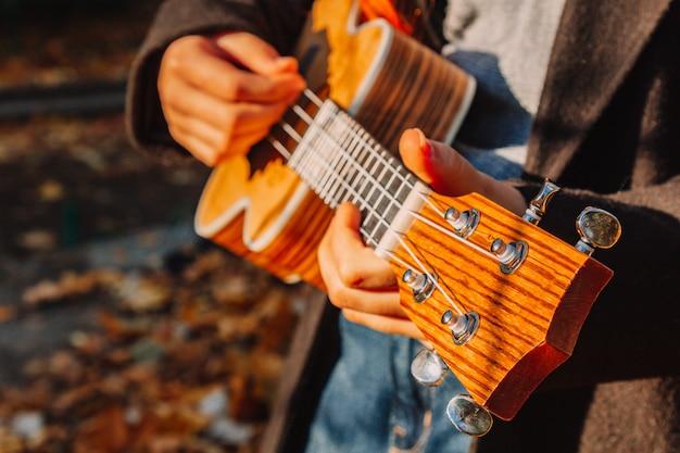 Garota ruiva com cabelos longos toca ukulele no parque. escola, conceito de educação musical, o aluno aprende a tocar o instrumento de cordas. mãos de um músico, clássico, melodia, criatividade.