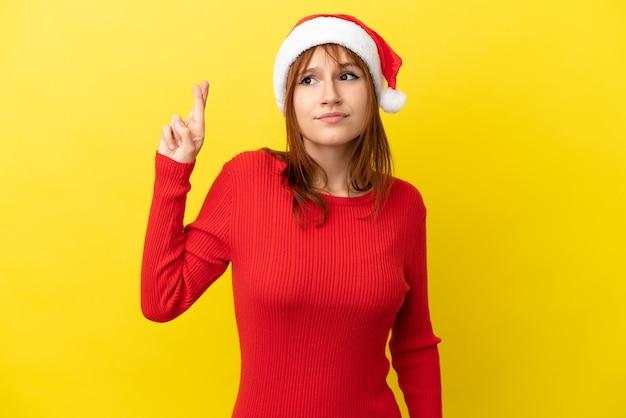 Garota ruiva com chapéu de natal isolada em fundo amarelo com dedos se cruzando e desejando o melhor
