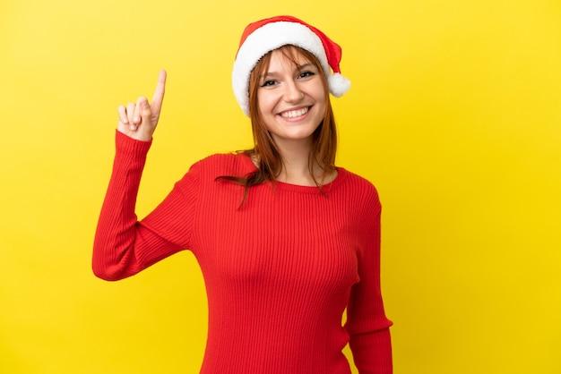 Garota ruiva com chapéu de natal isolada em um fundo amarelo apontando uma ótima ideia