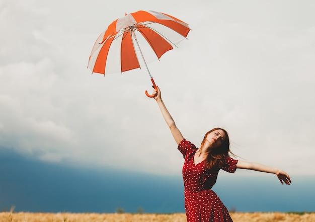 Garota ruiva com guarda-chuva no campo