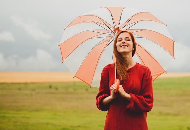 Garota ruiva com guarda-chuva no prado