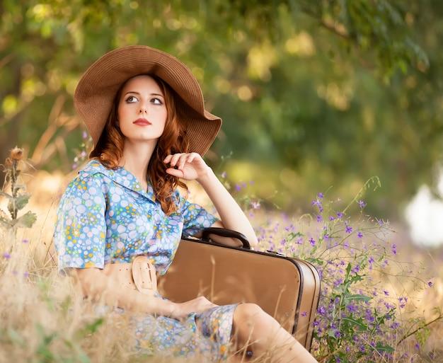 Garota ruiva com mala sentado na grama de outono