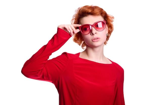 Garota ruiva com roupas vermelhas ajeitando os óculos rosa