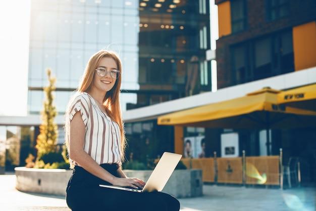 Garota ruiva com sardas olhando através de óculos está sentada em um banco em frente ao prédio e usando um laptop
