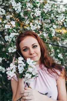 Garota ruiva com sardas perto da macieira