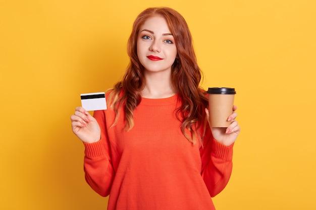 Garota ruiva com suéter laranja fica com café para viagem nas mãos, compras online, adorável senhora posando com espaço amarelo isolado,