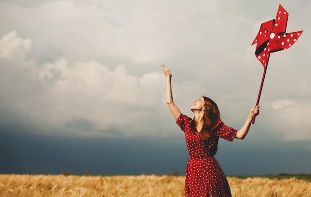 Garota ruiva com turbina de vento de brinquedo