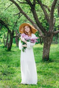 Garota ruiva com um buquê de lilases em um jardim de primavera