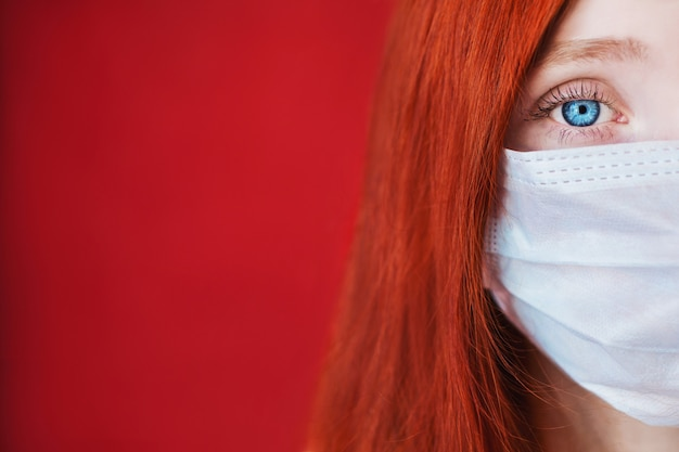 Garota ruiva com uma máscara médica em um copyspace vermelho, médico da mulher, mulher com olhar intenso, europeu, metade do rosto, cabelos soltos